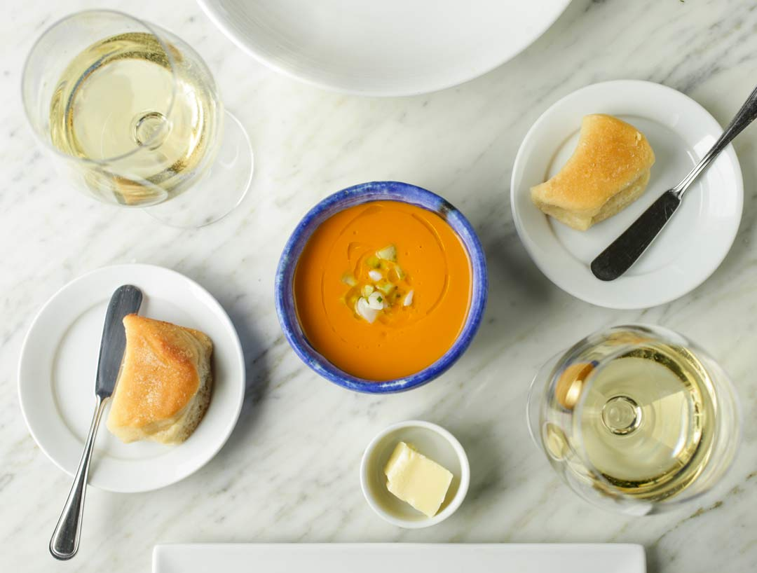Gazpacho on a table with bread, butter and a glass of wine