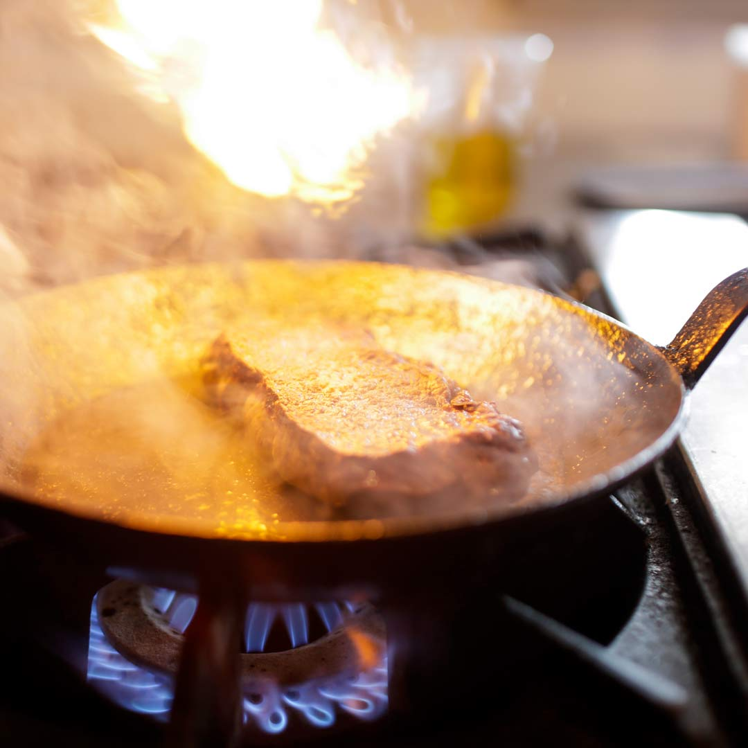 Steak cooking on a flaming skillet